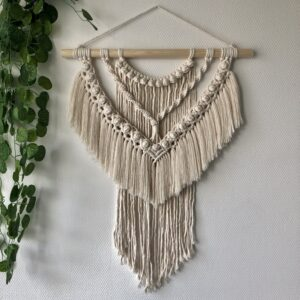 "Macrame wandhanger ""Kees"" in naturel met links in de hoek een hangplant ter decoratie"