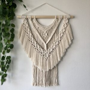 "Macrame wandhanger ""Ligia"" in naturel met links in de hoek een hangplant ter decoratie"